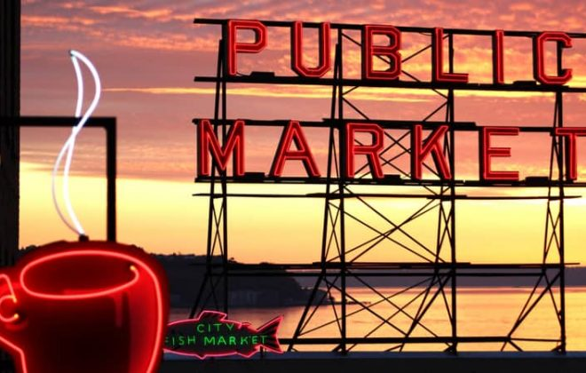 The neon Pike Place Market sign with the sunset in the background